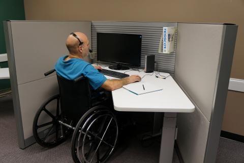كيفية استخدام بطاقة الخدمات المتكاملة -صورة رجل من ذوي الاحتياجات الخاصة في عمله